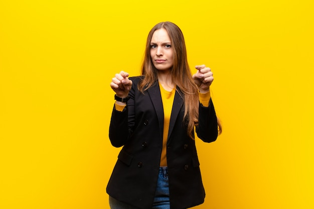 Young pretty businesswoman pointing forward at camera with both fingers and angry expression, telling you to do your duty on orange