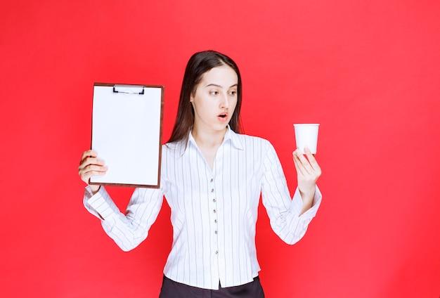 Piuttosto giovane imprenditrice in posa con appunti vuoti e bicchiere di plastica.