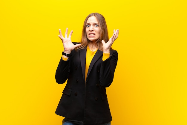 Young pretty businesswoman screaming with hands up in the air, feeling furious, frustrated, stressed and upset against orange wall