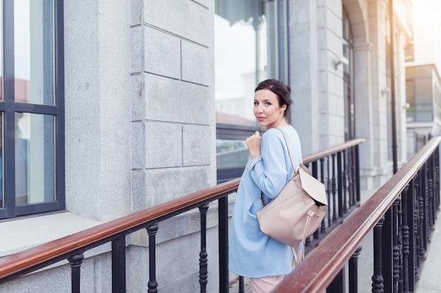 웃 고 비즈니스 건물 근처 걷는 젊은 예쁜 사업가. 그녀는 파트너와의 성공적인 회의 후 걷고 있습니다.