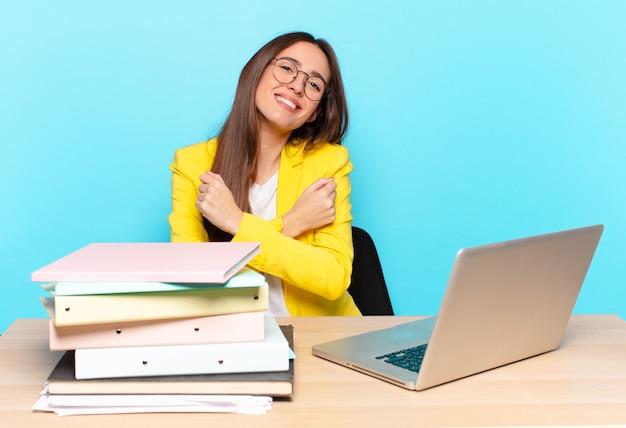 Молодая красивая деловая женщина весело улыбается и празднует со сжатыми кулаками и скрещенными руками, чувствуя себя счастливой и позитивной