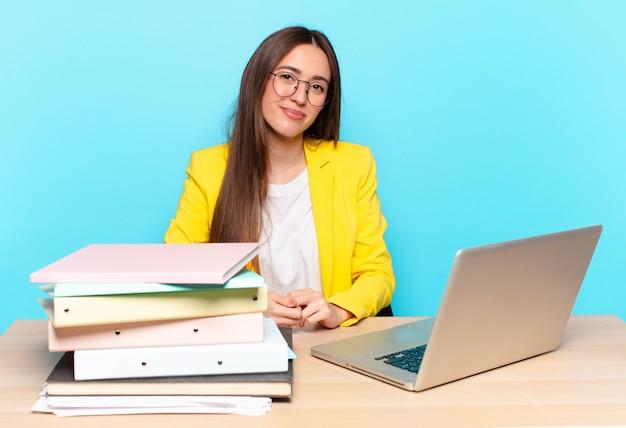 Молодая красивая деловая женщина улыбается позитивно и уверенно, выглядит довольной, дружелюбной и счастливой