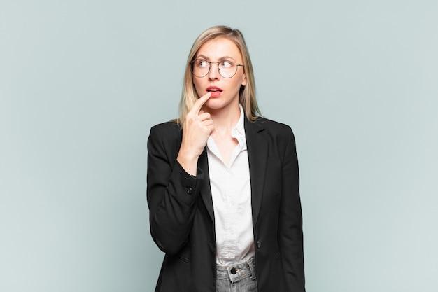 Молодая красивая деловая женщина с удивленным, нервным, встревоженным или испуганным взглядом смотрит в сторону в сторону копии пространства