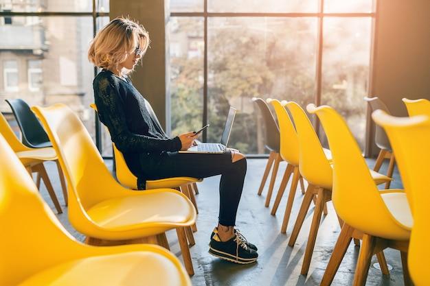 Молодая довольно занятая женщина сидит одна в конференц-зале, много желтых стульев, работает на ноутбуке