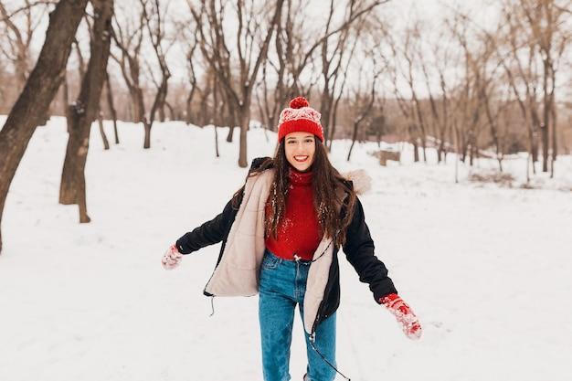 赤いミトンと帽子をかぶった若いかなり率直な笑顔の幸せな女性は、暖かい服を着て雪の中で公園で遊んで歩いて、楽しんで