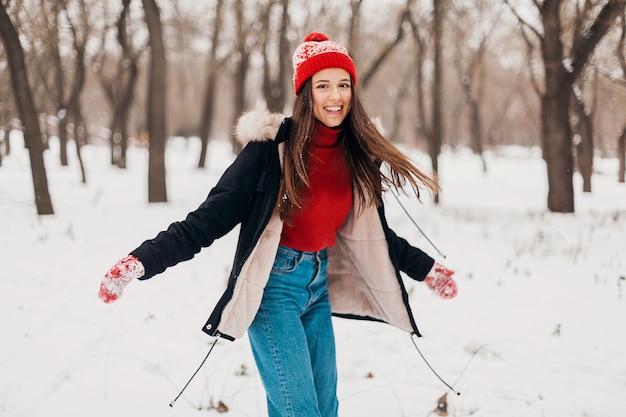 赤いミトンと帽子をかぶった若いかなり率直な笑顔の幸せな女性は、暖かい服を着て雪の中で公園で遊んで、楽しんで歩いて黒いコートを着ています