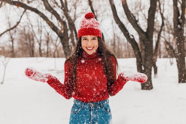 赤いミトンと帽子をかぶった若いかなり率直な笑顔の幸せな女性は、雪の中で公園で遊んで、暖かい服を着て、楽しんで、ニットのセーターを着て歩いています