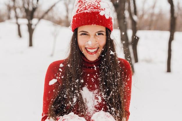 Молодая довольно откровенная улыбающаяся счастливая женщина в красных рукавицах и шляпе, носящая вязаный свитер, гуляет, играя в парке в снегу, теплой одежде, веселится