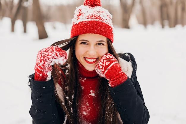 Молодая довольно откровенная улыбающаяся счастливая женщина в красных рукавицах и вязаной шапке в черном пальто гуляет, играя в парке в снегу, теплой одежде, веселится