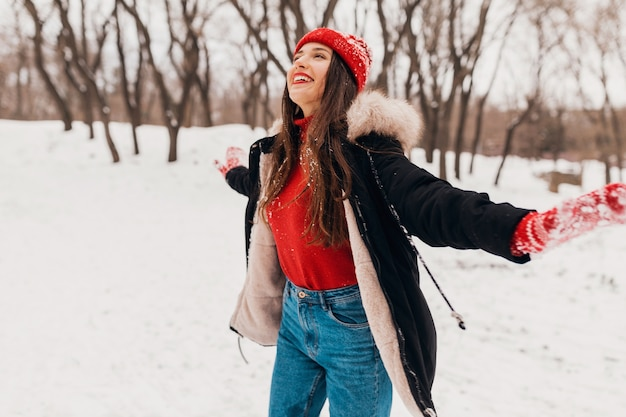 Young pretty candid smiling happy woman in red mittens and hat wearing black coat walking playing in park in snow in warm clothes, having fun