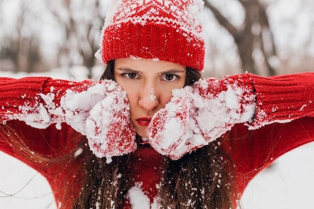 Giovane donna felice sorridente abbastanza candida in guanti rossi e cappello che indossa maglione lavorato a maglia a piedi giocando nel parco nella neve, vestiti caldi, divertendosi, faccia buffa seria