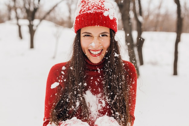 Young pretty candid smiling happy woman in red mittens and hat wearing knitted sweater walking playing in park in snow, warm clothes, having fun