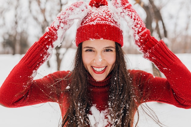 Giovane donna felice sorridente abbastanza candida in guanti rossi e cappello che indossa un maglione lavorato a maglia a piedi giocando nel parco nella neve, vestiti caldi, divertendosi