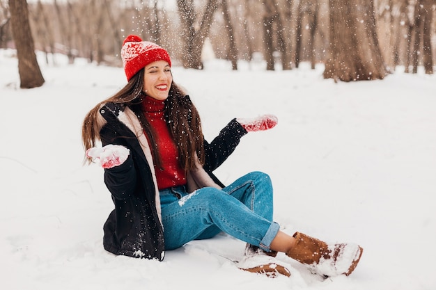 Young pretty candid smiling happy woman in red mittens and knitted hat wearing black coat walking playing in park in snow, warm clothes, having fun