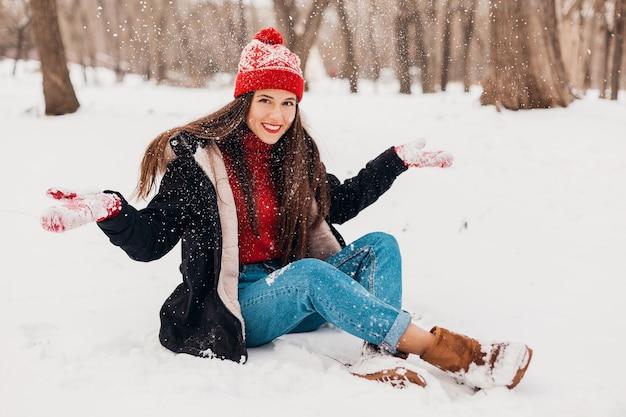 Giovane donna felice sorridente abbastanza candida in guanti rossi e cappello lavorato a maglia che indossa cappotto nero che cammina giocando nel parco nella neve, vestiti caldi, divertendosi