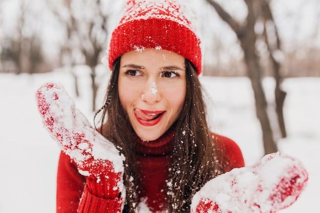 Giovane donna felice sorridente abbastanza candida con espressione faccia buffa in guanti rossi e cappello che indossa maglione lavorato a maglia a piedi giocando nel parco nella neve, vestiti caldi, divertendosi