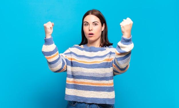 승자처럼 믿기지 않는 성공을 축하하는 젊은 예쁜 캐주얼 여성, 흥분되고 행복해 보이는 모습을 보며 그것을 받아보세요!