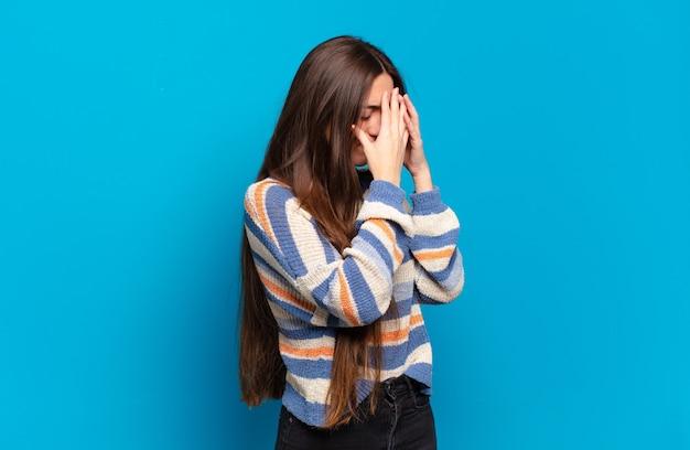 悲しくて欲求不満の絶望、泣き、側面図で目を覆っているかなりカジュアルな若い女性