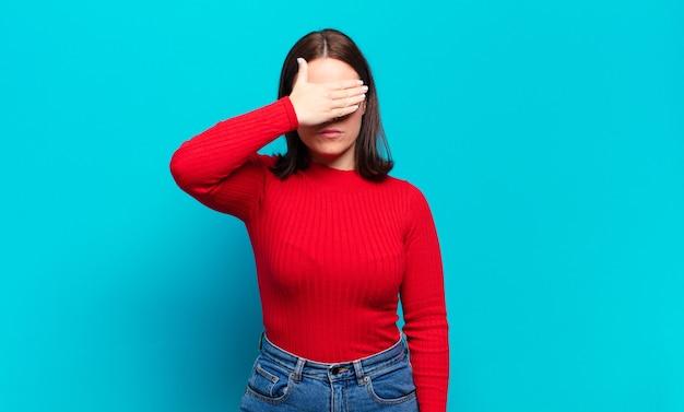 Молодая довольно повседневная женщина закрыла глаза одной рукой, чувствуя испуг или беспокойство, недоумевая или слепо ожидая сюрприза