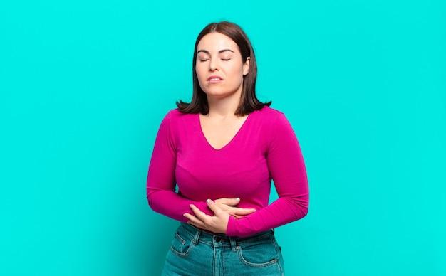 不安、病気、病気、不幸を感じ、痛みを伴う腹痛やインフルエンザに苦しんでいる若いかなりカジュアルな女性