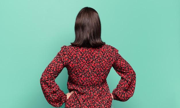 어리고 캐주얼한 여성은 혼란스럽거나 가득 차거나 의심과 질문을 하고 엉덩이에 손을 얹고 후면을 봅니다.
