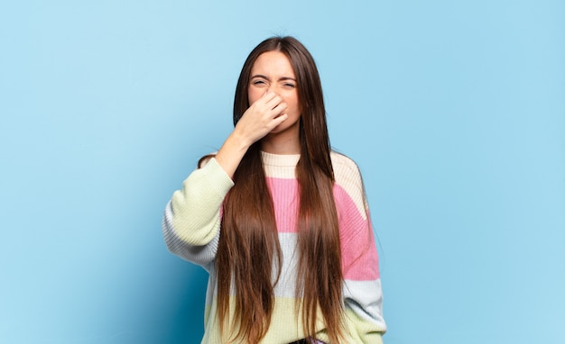 Young pretty casual woman feeling disgusted, holding nose to avoid smelling a foul and unpleasant stench