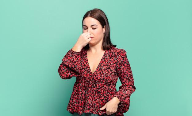 혐오감을 느끼는 젊은 꽤 캐주얼 여성, 파울하고 불쾌한 악취를 피하기 위해 코를 잡고