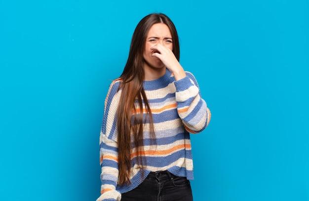 嫌悪感を感じ、悪臭や不快な悪臭を避けるために鼻をかむ若いかなりカジュアルな女性