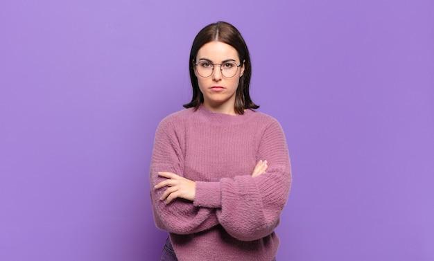 Молодая довольно непринужденная женщина чувствует себя недовольной и разочарованной, выглядит серьезной, раздраженной и сердитой со скрещенными руками