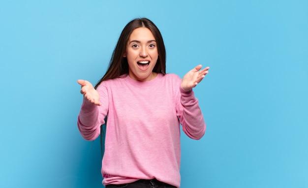 Молодая довольно непринужденная женщина чувствует себя счастливой, удивленной, удачливой и удивленной, как будто серьезно говорит: «боже»? невероятный