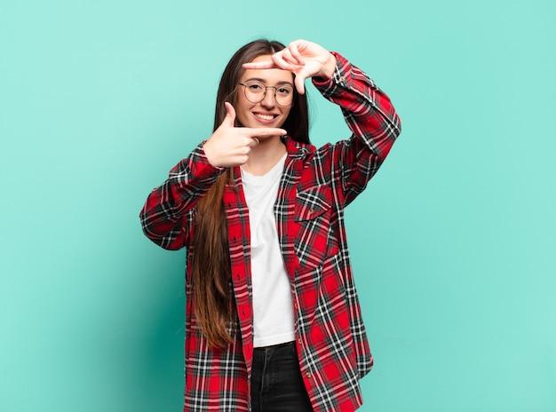 Молодая довольно повседневная женщина чувствует себя счастливой, дружелюбной и позитивной, улыбается и делает портрет или фоторамку руками