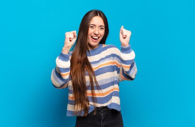 Молодая довольно повседневная женщина чувствует себя счастливой, позитивной и успешной, празднует победу, достижения или удачу