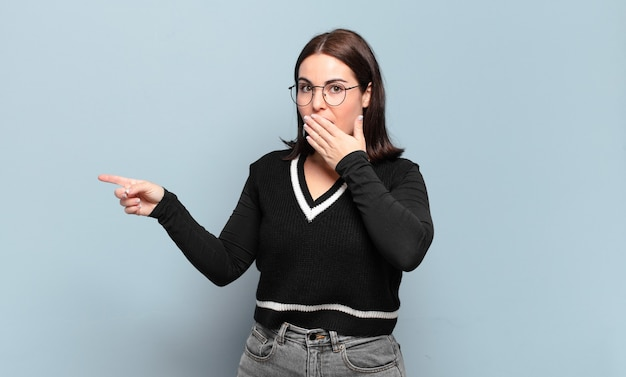 Young pretty casual woman feeling happy, shocked and surprised, covering mouth with hand and pointing to lateral copy space