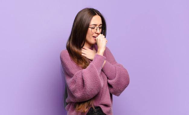 Молодая довольно непринужденная женщина чувствует себя плохо, с симптомами гриппа и болью в горле, кашляет с прикрытым ртом