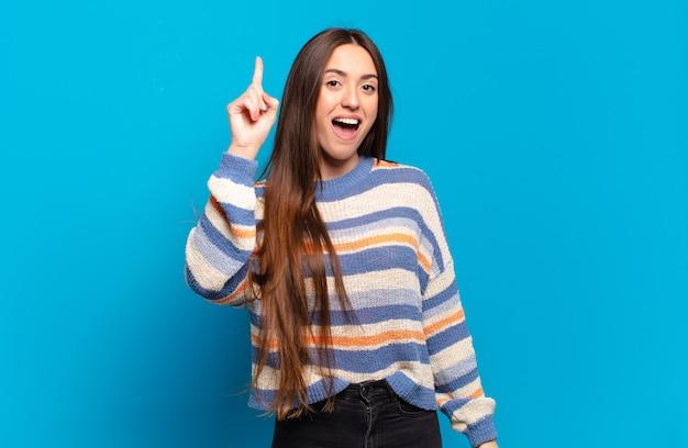 Молодая довольно-таки непринужденная женщина чувствует себя счастливым и взволнованным гением, реализовав идею, весело подняв палец, эврика!