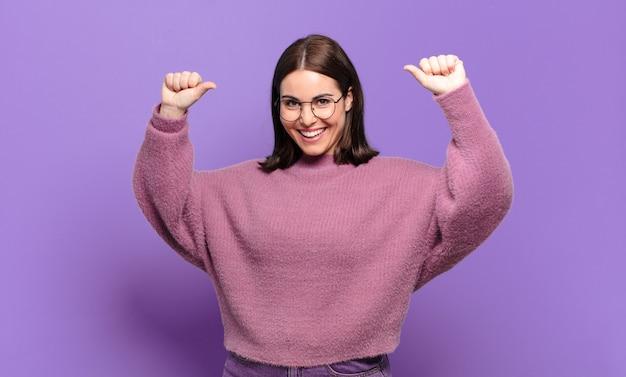 자랑스럽고 오만하고 자신감이 넘치고 만족스럽고 성공한 느낌, 자기를 가리키는 젊은 꽤 캐주얼 여성