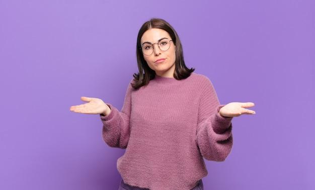 Молодая довольно непринужденная женщина чувствует себя озадаченной и сбитой с толку, неуверенной в правильном ответе или решении, пытаясь сделать выбор