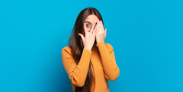 Молодая довольно непринужденная женщина чувствует себя напуганной или смущенной, подглядывает или шпионит с полуприкрытыми руками глазами