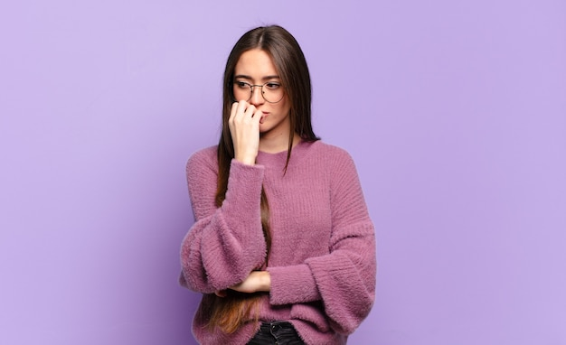 Young pretty casual woman feeling serious, thoughtful and concerned, staring sideways with hand pressed against chin