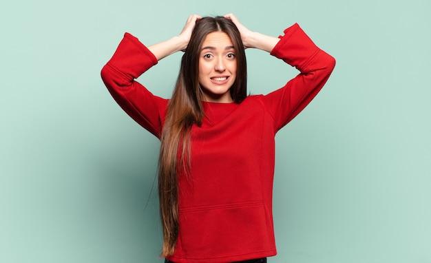 Молодая довольно непринужденная женщина чувствует стресс, беспокойство, тревогу или страх, с руками за голову, паникует из-за ошибки
