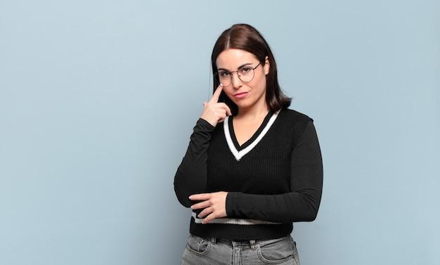 Молодая довольно непринужденная женщина присматривает за вами, не доверяя, наблюдая и оставаясь бдительной и бдительной