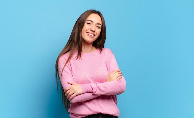 Молодая довольно непринужденная женщина счастливо смеется, скрестив руки, в расслабленной, позитивной и удовлетворенной позе