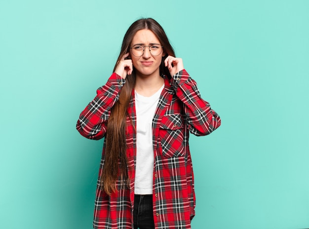 怒り、ストレス、イライラしているように見え、耳をつんざくような音、音、または大音量の音楽で両耳を覆っている、かなりカジュアルな若い女性