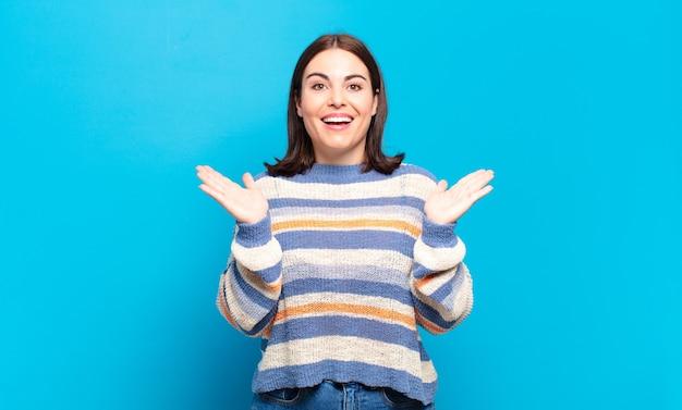 Молодая довольно непринужденная женщина выглядит счастливой и взволнованной, потрясенной неожиданным сюрпризом, с открытыми руками рядом с лицом
