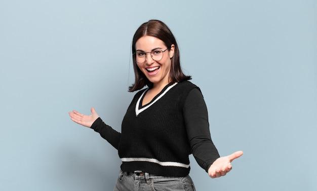 Молодая довольно непринужденная женщина выглядит счастливой, высокомерной, гордой и самодовольной, чувствуя себя номером один