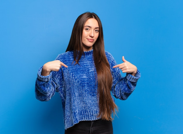 Young pretty casual woman looking proud, positive and casual pointing to chest with both hands
