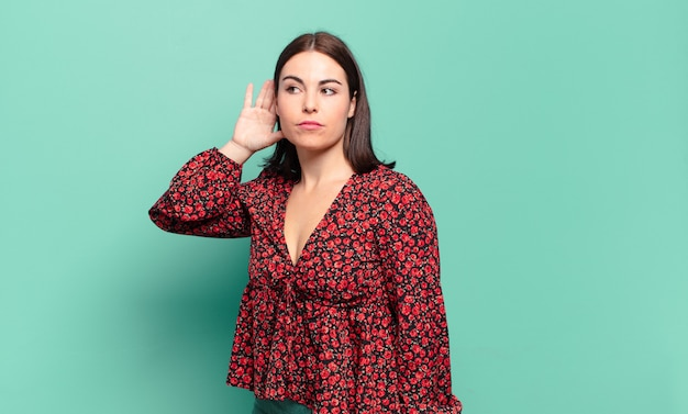Молодая довольно непринужденная женщина выглядит серьезной и любопытной, слушает, пытается услышать секретный разговор или сплетню, подслушивает