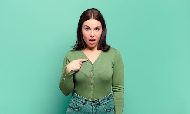 Молодая довольно непринужденная женщина выглядит шокированной и удивленной с широко открытым ртом, указывая на себя