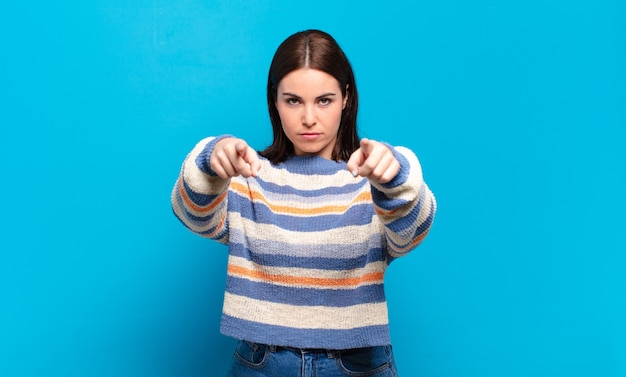 指と怒りの表情の両方で前を向いて、あなたにあなたの義務を果たすように言っている若いかなりカジュアルな女性