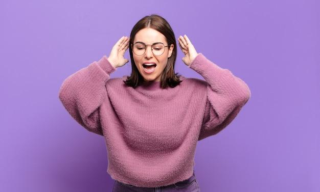 Молодая довольно непринужденная женщина кричит от паники или гнева, шокирована, напугана или разъярена, положив руки на голову